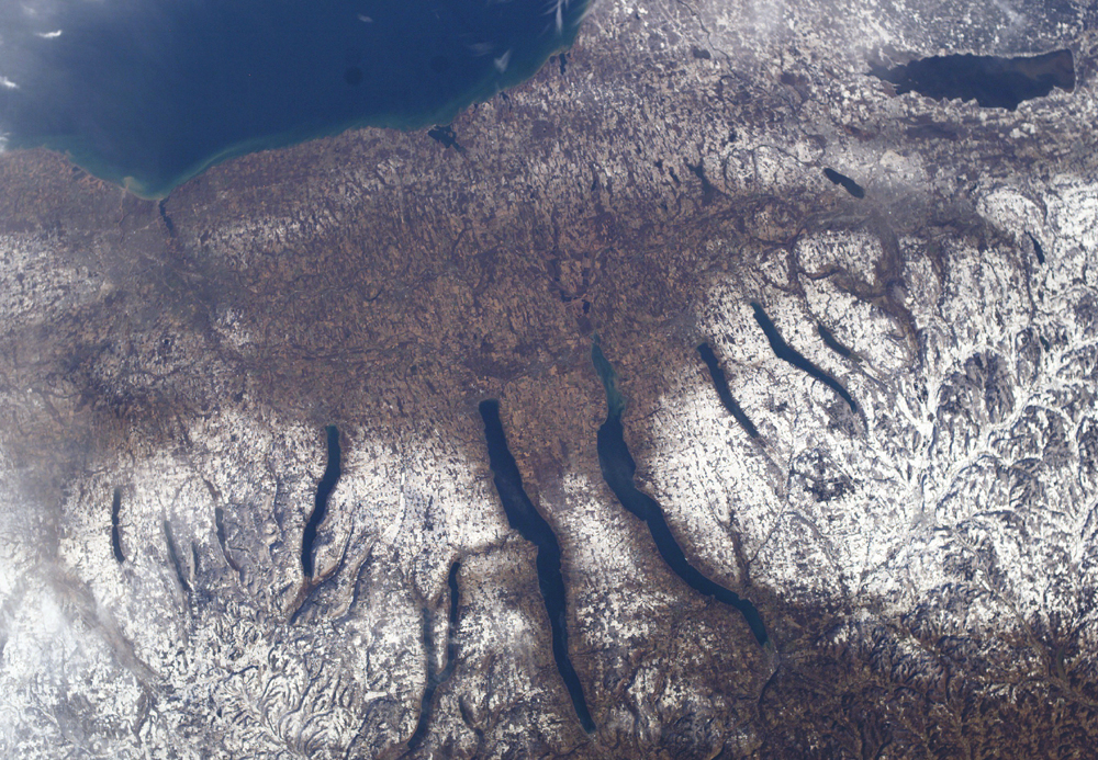 A satellite photo of the Finger Lakes region of NY with regions covered in snow