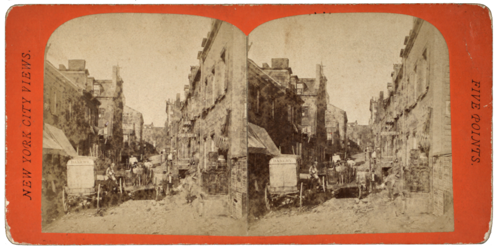 A stereoscopic black and white photograph of a street in Five Points. The view looks down the middle of a dirt covered street with horse-drawn carriages and stores.