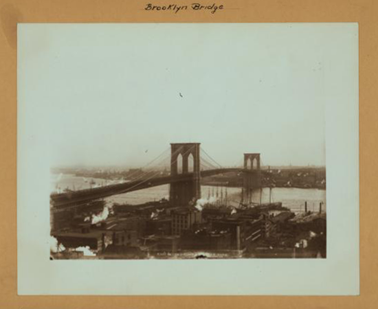 A black and white photograph of the Brooklyn Bridge and the surrounding parts of Manhattan.