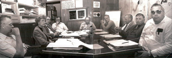 A black and white photograph of 8 men and 1 woman, all middle-late aged sitting around a table.