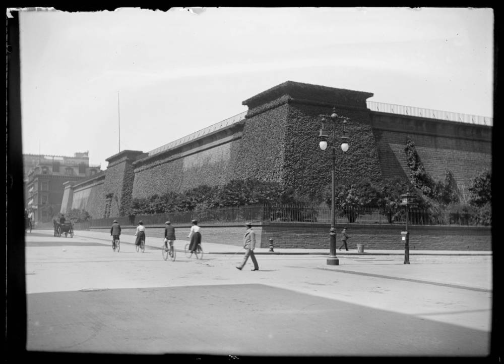 A black and white photograph of a large brick structure, about 10 stories high with no windows. The architectural style is Egyptian Revival. There are people walking around it. There are vines growing on the outside of the structure.