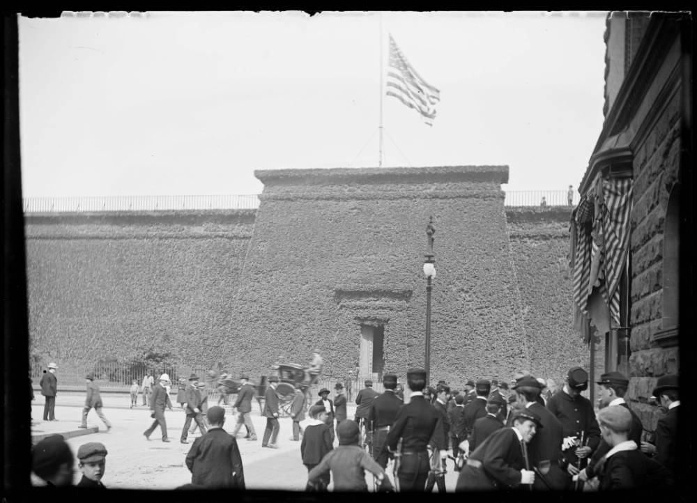 A black and white photograph of a large brick structure, about 10 stories high  a single entrance/door and no windows. There is an American flag atop the structure. There are people walking around it. There are vines growing on the outside of the structure.