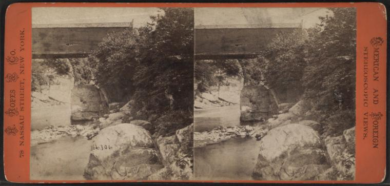 A stereoscopic black and white photo of a rocky river running under an overpass or bridge.