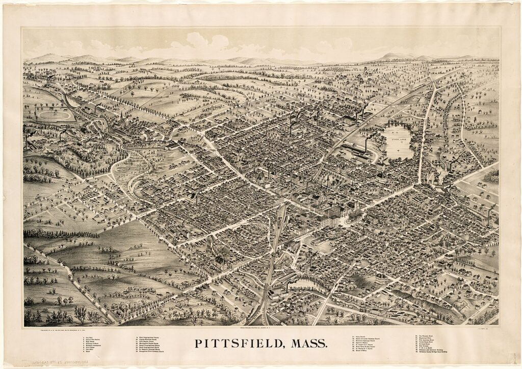 A black and white illustration of a birds-eye-view of a small down, Pittsfield. Houses and trees are visible in the foreground. A lake can be seen on the edge of town, and off in the distance are rolling hills.