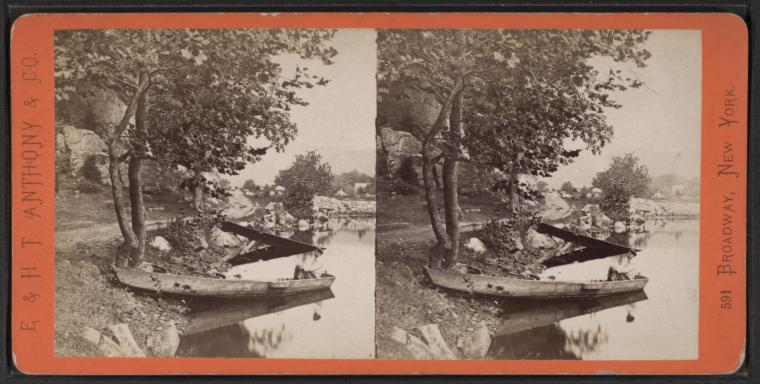 A stereographic image (two squares with the same photo placed-side-by-side intended to be viewed through a special viewer for a 3Dimensional effect) of a black and white landscape featuring a riverbank with a tree in the foreground. There are two canoes banked on the edge of the water.