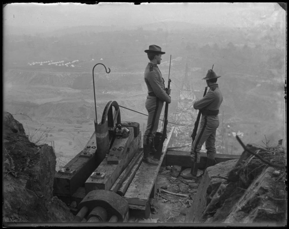 A black and white photo of two soldiers with rifles looking over a cliff into a foggy valley where the dam is being constructed. There is a tent village down in the valley and distant hills. The soldiers are standing near a crane wheel with a cable that drops down off the cliff edge down into the valley below.