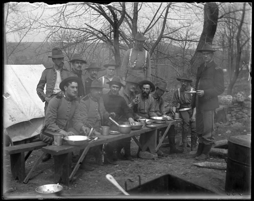 A black and white photograph of a group of soldiers sitting on a bench, some standing behind. They are sitting in a camp with bare trees and tents. Silverware, plates and bowls are set on a bench in front of the soldiers.