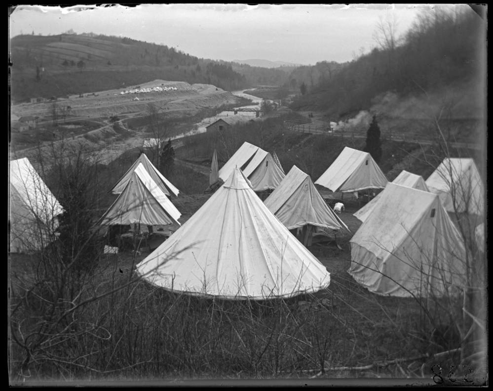 A black and white photograph of the valley where the dam was being constructed. A cluster of white canvas tents occupy the foreground. In the background there is the dam construction and more tents. Another cluster of tents is seen in the far background, and further in the view are distant hazy hills.