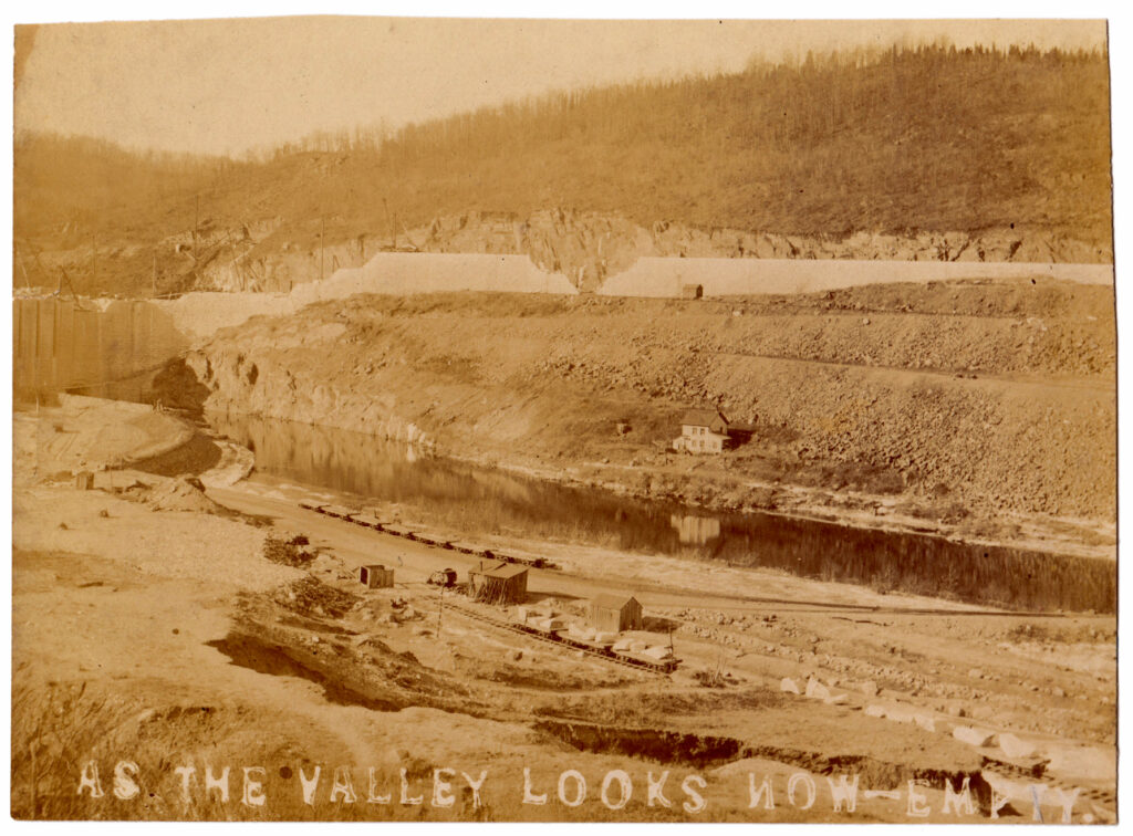 """An amber-tinted photograph looking down on a bare dirt valley. A partially-built dam wall surrounds the area where there is an area of water, a house, a shack and railroad lines. Text is stamped into the photo that says """"As the valley looks now - empty"""""""