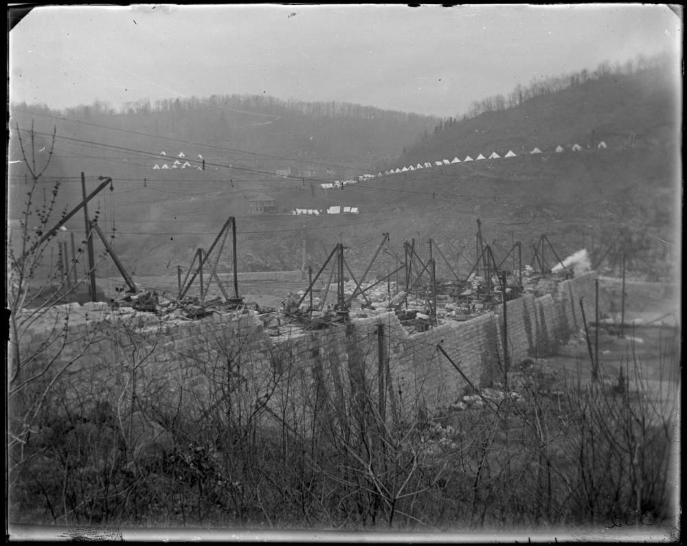 A black and white photo looking down from a hilltop to the valley below. The dam wall is under construction with crane-like steel armatures sitting atop a half-built wall that extends from  camera left down into the valley. On the distant hillsides on the otherside of the valley there are lines of teepee-like tents. It is winter, with bare trees visible on the far hills.