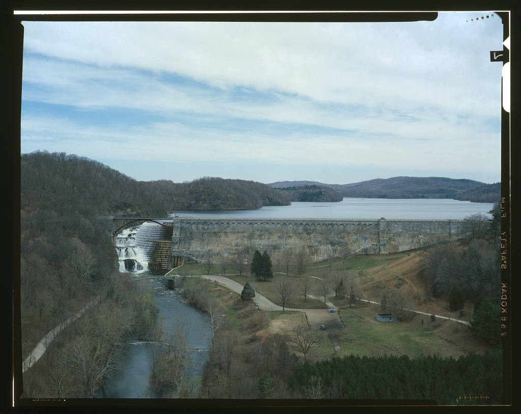 A color photograph made with a large format 4x5 camera (you can see the black frame lines bordering the image) of the New Croton Reservoir and Dam. The photo is taken from high up in the air. Mountains and hills surround the bodies of water.