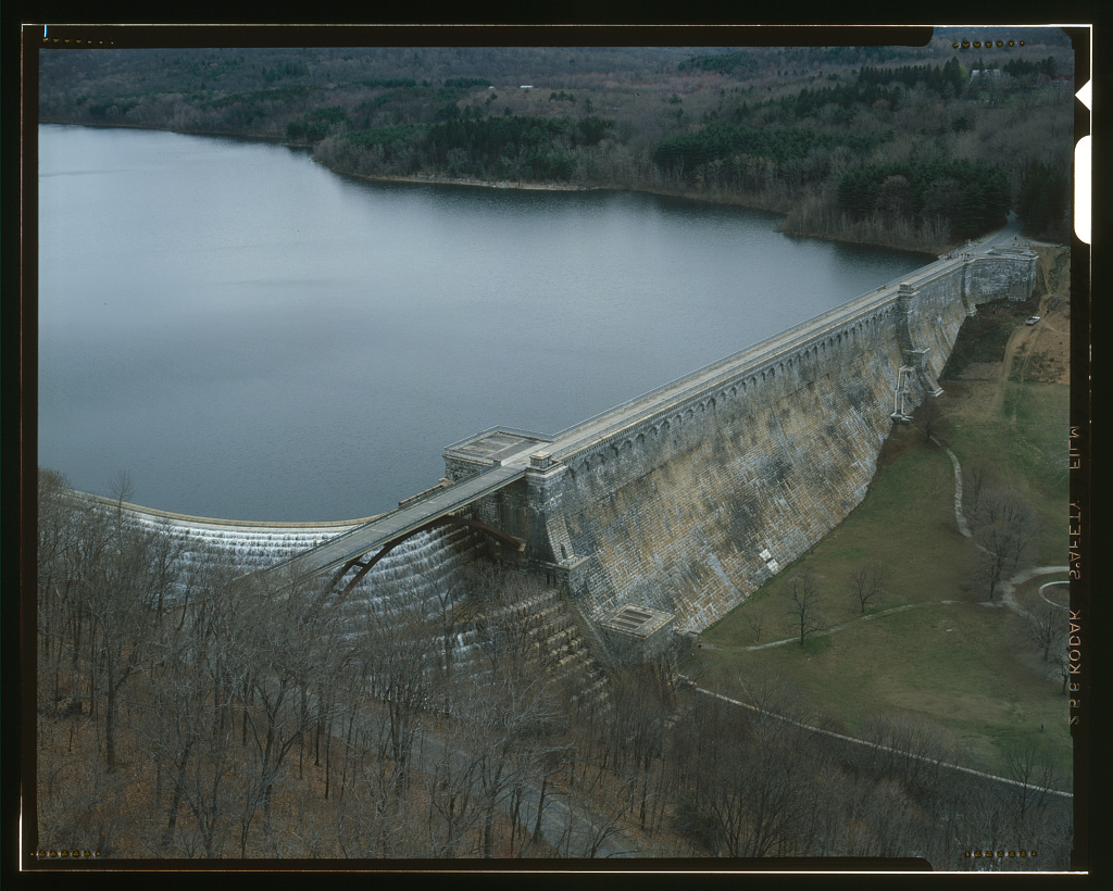 A color photograph made with a large format 4x5 camera (with black frame lines bordering the image) of the New Croton Reservoir and Dam. The photo is taken from high up in the air and closer to the dam wall.