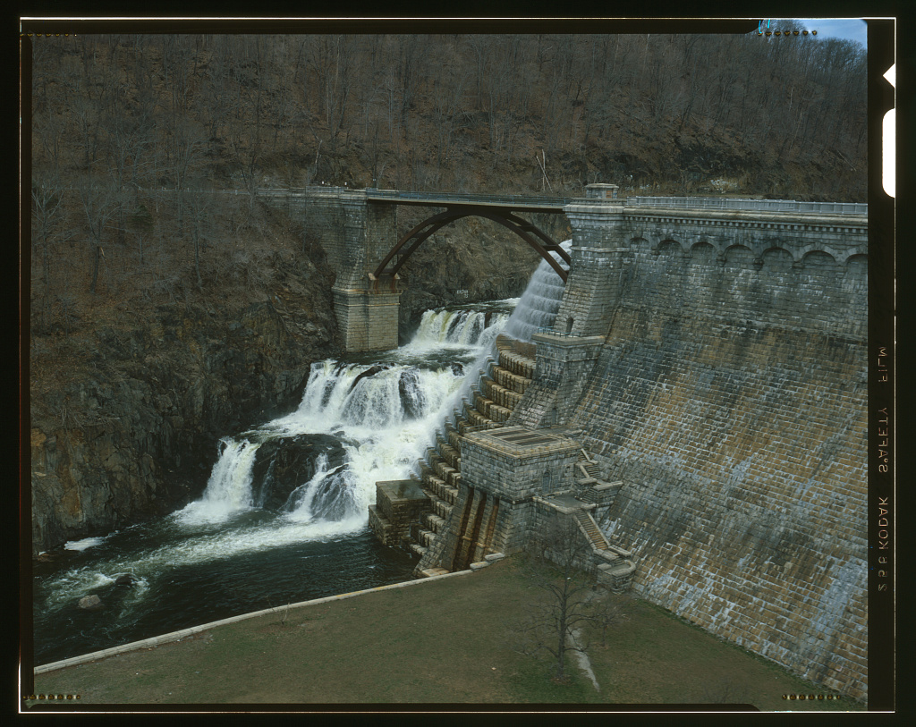 A color photograph made with a large format 4x5 camera (with black frame lines bordering the image) of the New Croton Reservoir and Dam. The view is similar to the previous photos but the camera is lower, on the same level as the top of the bridge, looking down to the waterfall.