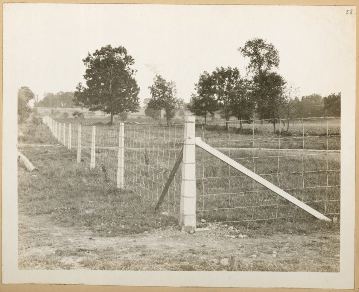 A black and white photo of a country setting. A corner of a fence is in the foreground with one side of the fence extending into the far distance on the left. The fence is made from timber posts and rectangular wire fencing.