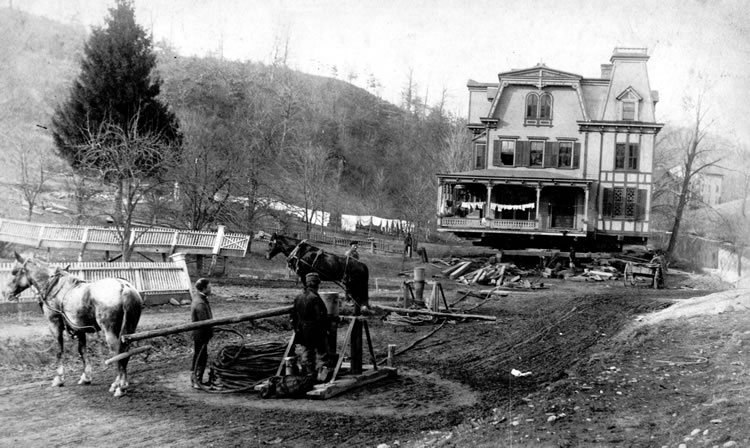 A black and white photograph of a three story house in the background, its foundation hovering above the ground below with logs at its base. In the foreground there are horses, men, and evidence of a pulley system with ropes.