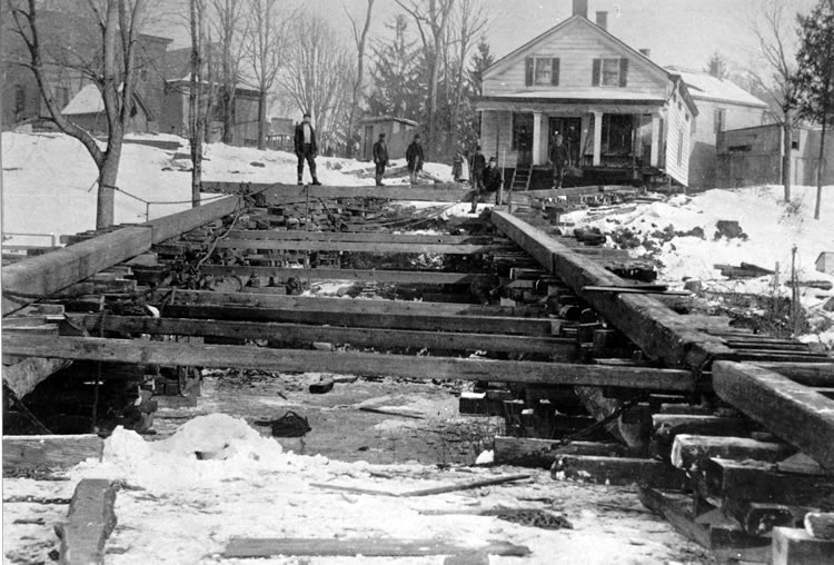 A black and white photo of a two-story house in the background. In the foreground there are rail tracks amongst a snowy winter scene. There are a few men in the background.