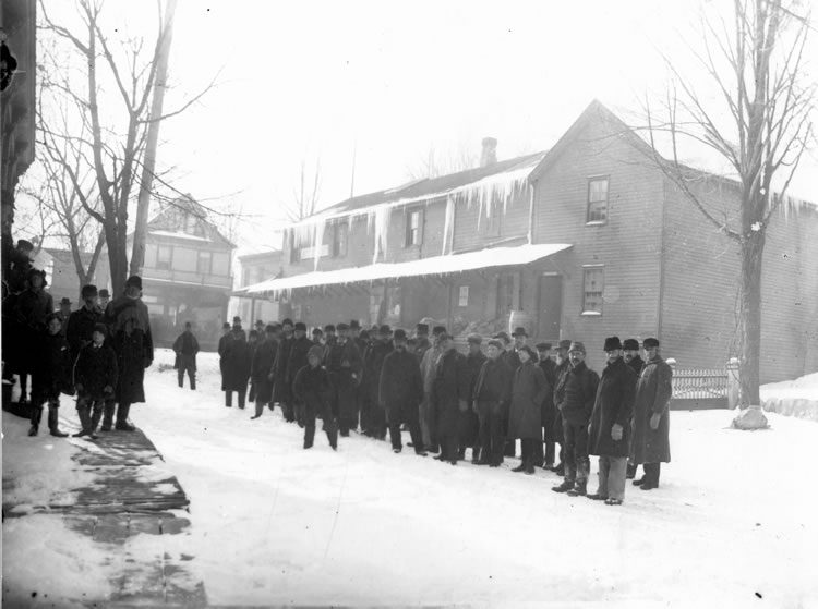 A black and white photo of a winter scene showing a group of men gathered in the middle of a snowy street. They are facing another group of people on the sidewalk. Most people are looking at the camera.