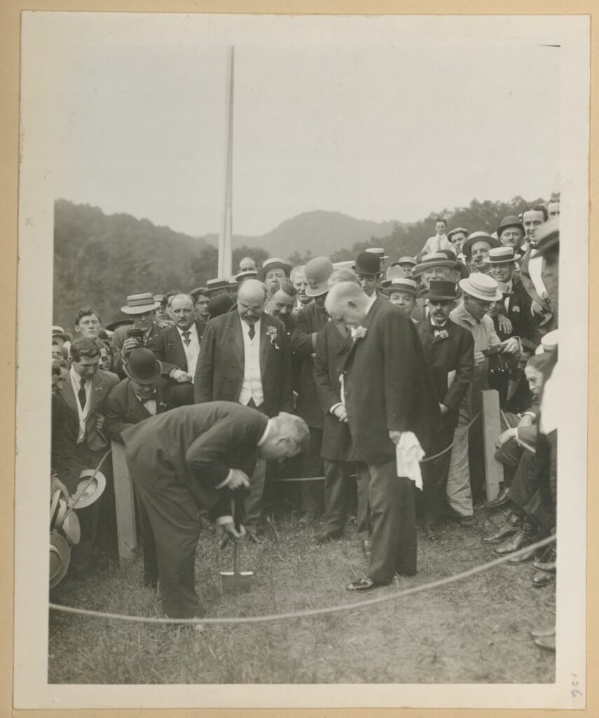 A photo of a crowd of white men in suits, bowlers hats, and period dress, gather around a roped off section of grass where a man is using a shovel to turn some grass.