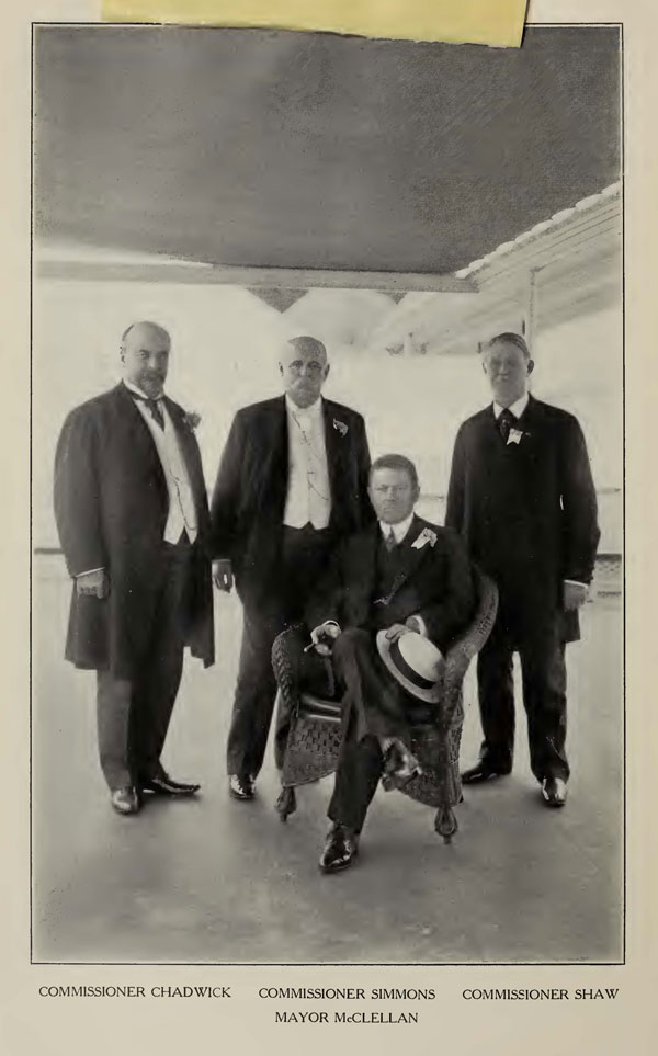 A black and white photo of four older white men in suits. One is sitting, the other are standing behind.