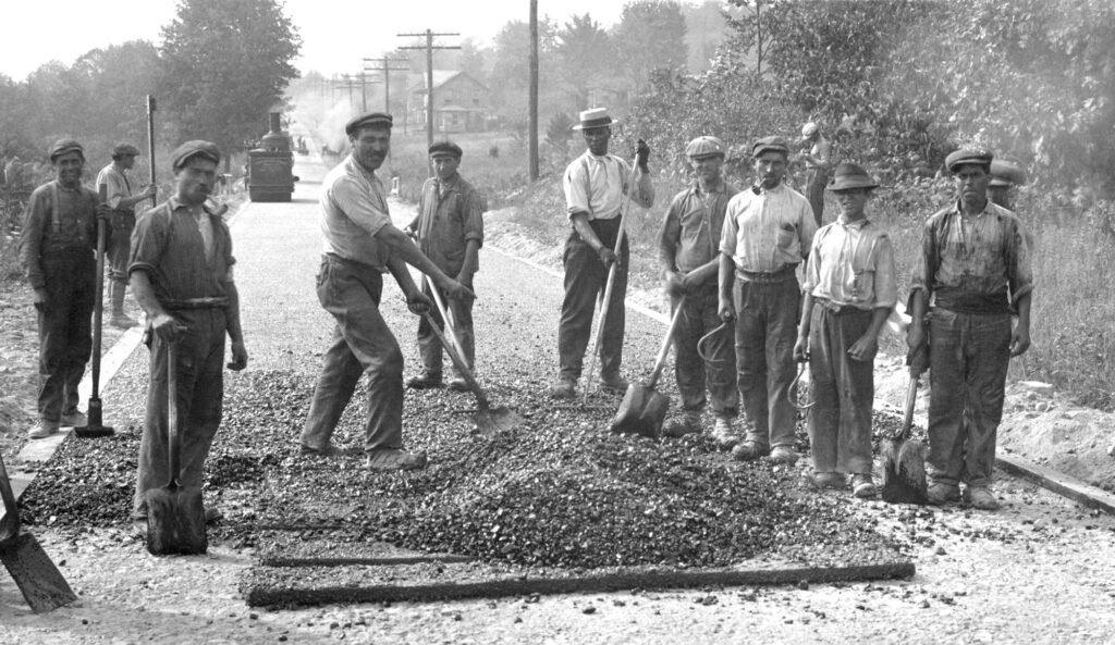 A black and white photo of a group of men standing around a pile of stones/bitumen on a country road. They are holding shovels and looking at the camera. The men are all wearing hats and have olive and dark skin tones.