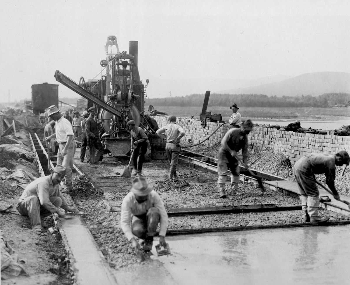 A black and white photo of laborers smoothing down concrete slabs. There is a machine in the background with workers working around and in front of it. A waist height brick wall separates the work from the background landscape which includes a body of water and a distant hazy mountain.