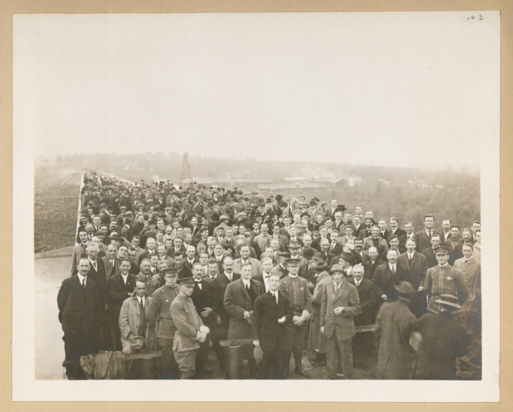 A black and white photo of a large crowd of white men on a bridge looking at the camera which is up high. Some buildings can be seen in the distance.