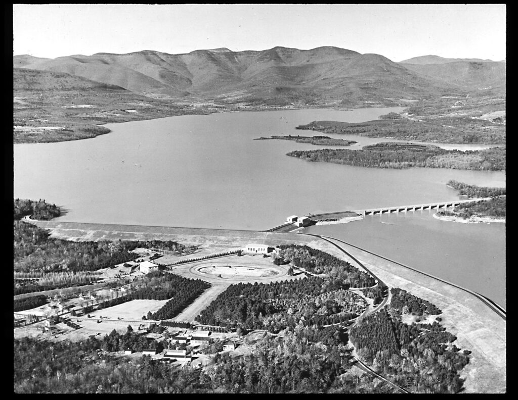 A bird's eye aerial black and white photo of the Ashokan Reservoir with a mountain range in the background. The body of water in the middle, and man-made circular structure and landscaped features in the foreground. A bridge stretches across from the foreground land to another edge of the water on the right.