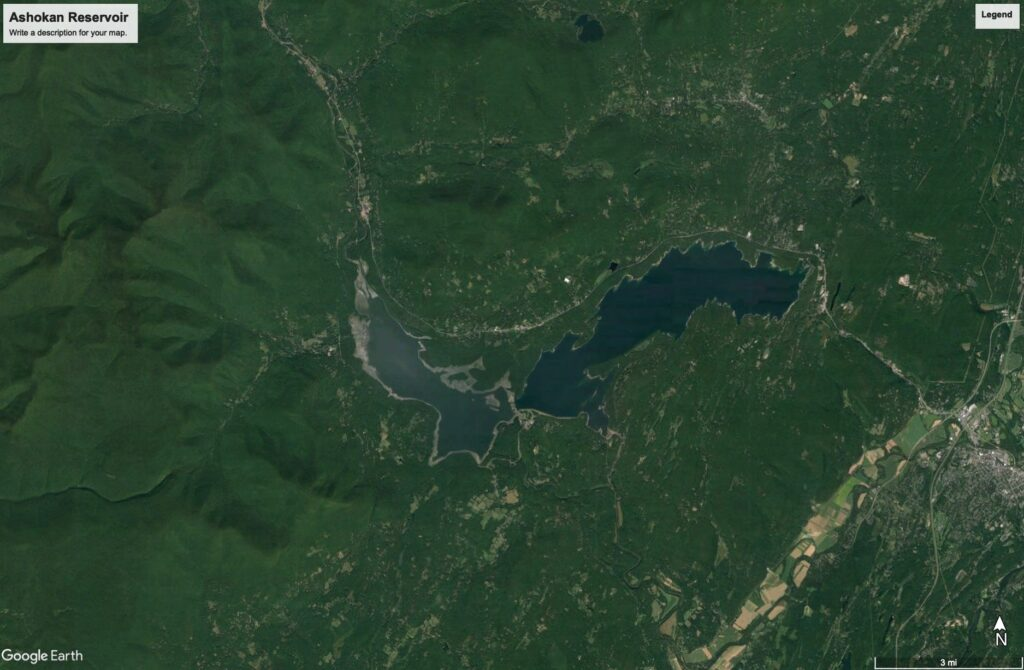 A satellite image that frames the Ashokan Reservoir and the topography of the Catskill Mountains that surround it. Like the images that precede it, it is mostly green forest, topography, and a dark blue form that represents the water.