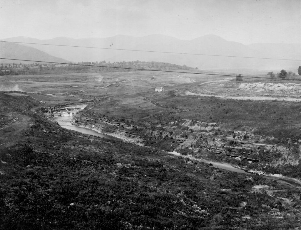 A black and white photo of an almost bare valley. There is a creek that cuts through the land and falls with horizontal rock strata embedded in the sides. A couple of houses dot the landscape and a mountain range is barely visible through a haze.