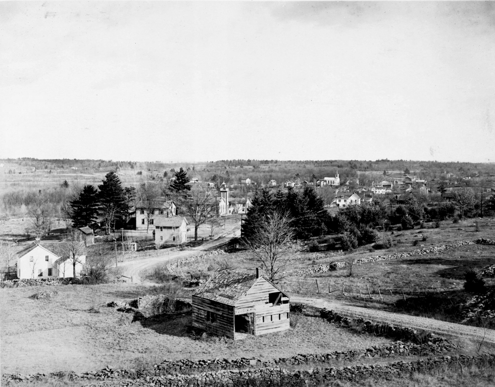 A black and white photo of a landscape dotted with country houses, dilapitated sheds, and in the distance, a church steeple. The photo is taken from up on a hill of a lightly hilled landscape. It is winter as the deciduous trees are bare.