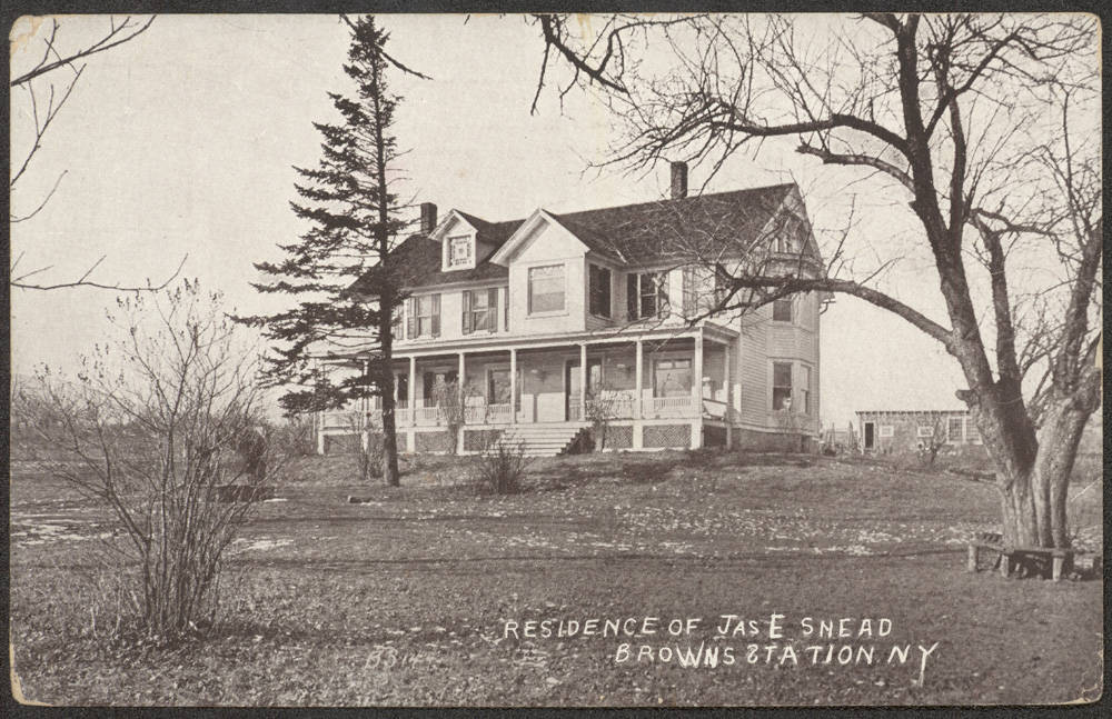 A black and white photo during winter time of a two story white house with a wide front porch and two chimneys. There are a few bare trees around and one tall evergreen tree.