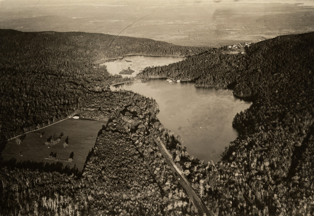 An aerial black and white photo of the Ashokan Reservoir nestled into the mountain landscape. The angle of the shadows is extreme and enhances the three dimensionality of the photo. The angle of the shadows indicates the photo was taken late afternoon.