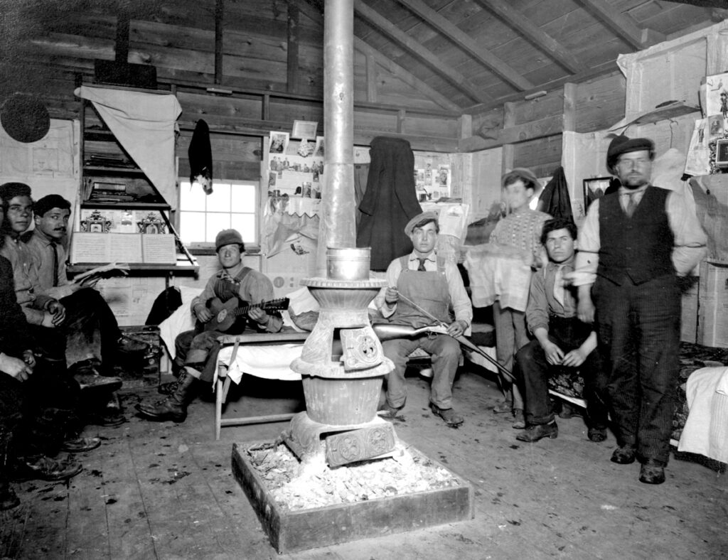 A black and white photo of the inside of a wood cabin. In the middle of the room there is a coal stove. Seven men are sitting and standing around the stove looking at the camera. One man is holding a guitar and another man is cleaning a rifle.