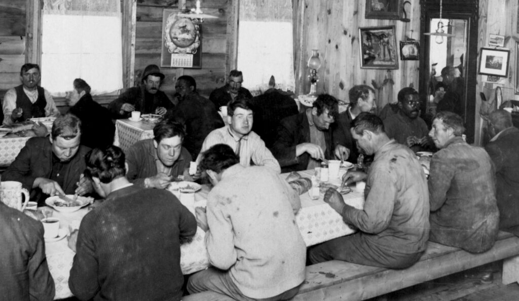 A black and white photo of a mess hall with wood walls. There are men eating a meal at communal tables. The include both white and Black men sharing space. They are all wearing dirty work clothes.