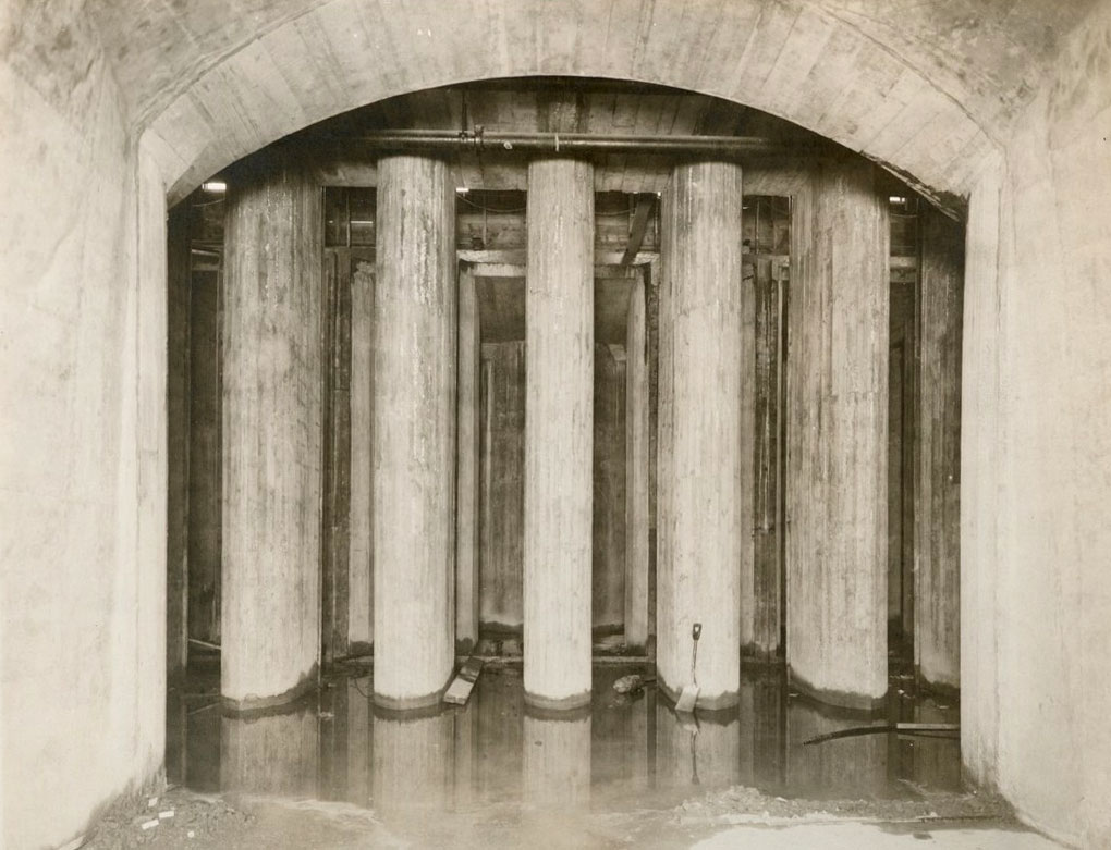 A black and white photo of an underground concrete tunnel with a high arched ceiling. At the end of the tunnel there are a grid of concrete columns, 5 across and others lined up behind the first row. There's a little water in the tunnel with a shovel leaning against one of the columns.