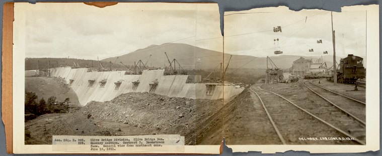 A black and white photo made up of two photos pasted together onto a backing board. The photo is old and has worn and frayed edges. The photo depicts a concrete dam wall under construction in the foreground, and railway tracks on the right foreground. A large mountain is in the background.