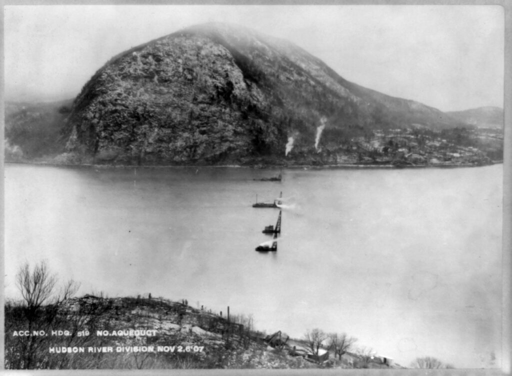 A black and white photo taken from high on a mountain overlooking the Hudson River below. There is a rounded mountain on the other side of the river, right on the edge of the shore. There are plumes of smoke rising from the shore. Four structures forming a row across the river rise from the water.