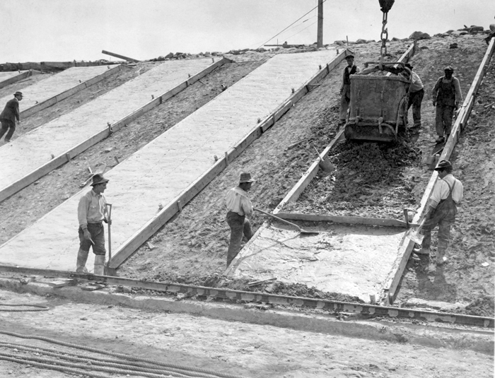 A black and white photo taken from the bottom of a sloping hill. Concrete slabs are being laid alongside its face. There is a suspended bucket in the process of delivering concrete and a handful of men working on the hill.