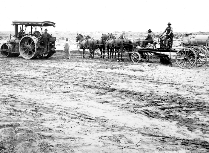 A black and white photo of a raw grassless and treeless plain. There a steamroller on the left and a horse-drawn cart on the right with men mounted on both.