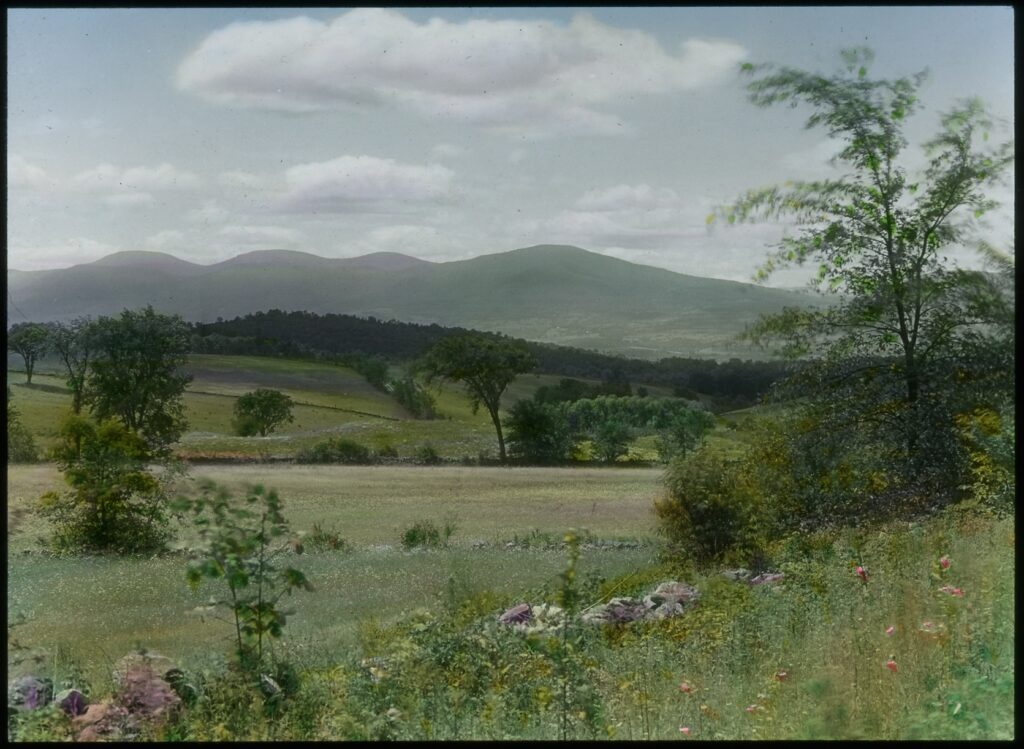 A hand-tinted color photograph of a pastoral landscape with with open fields and rolling hills in the foreground and the Catskill mountains on the horizon.