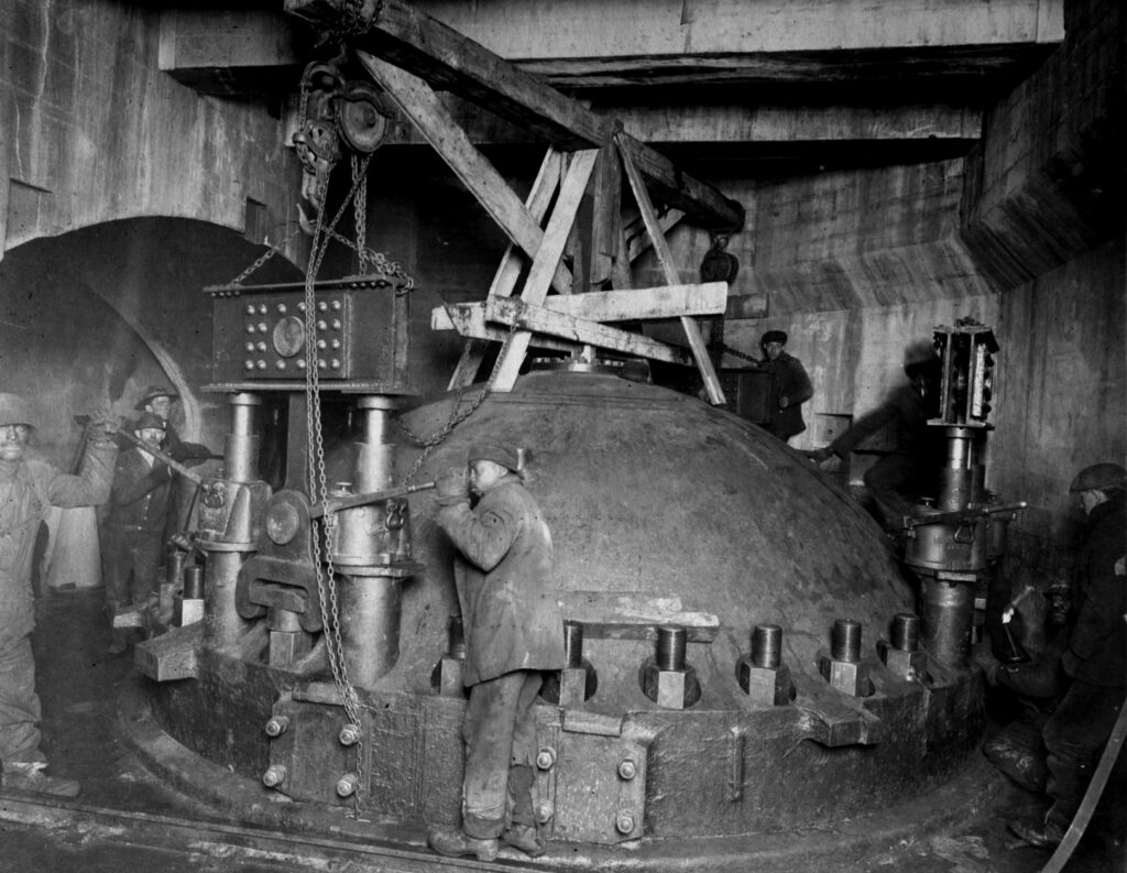 A black and white photo of an underground chamber where men, both Black and white, are handling equipment surrounding a large steel dome structure that looks to be about 10ft tall. A ring of massive bolts, about the size of a man's head are dotted around the base of the dome.