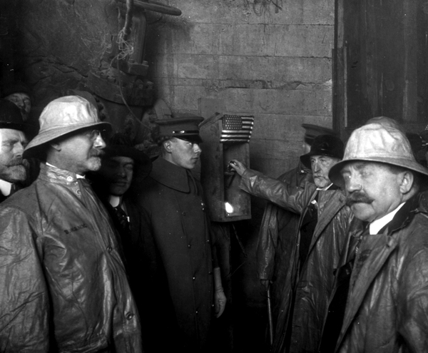 A black and white photo of five men standing around a wooden box with a hand-pulled lever in it. The men are wearing hard hats and some are uniform hats. A man has his hand on the lever about to pull it.