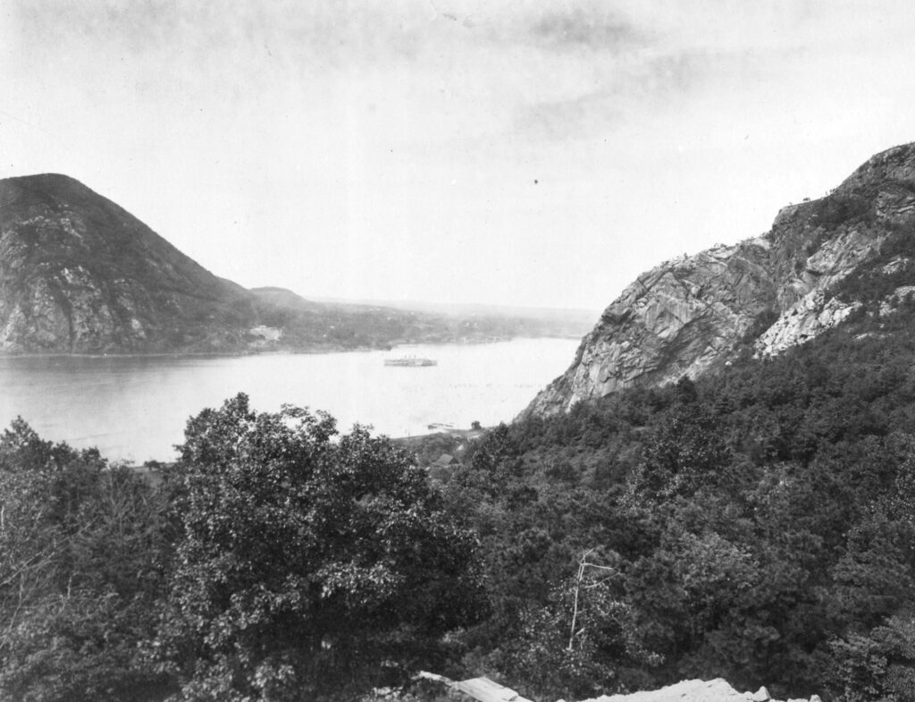 A black and white photo looking at a landscape from a high perspective. Below is a river surrounded on both sides by cliffed mountains. The sky and surface of the water looks misty and moody.