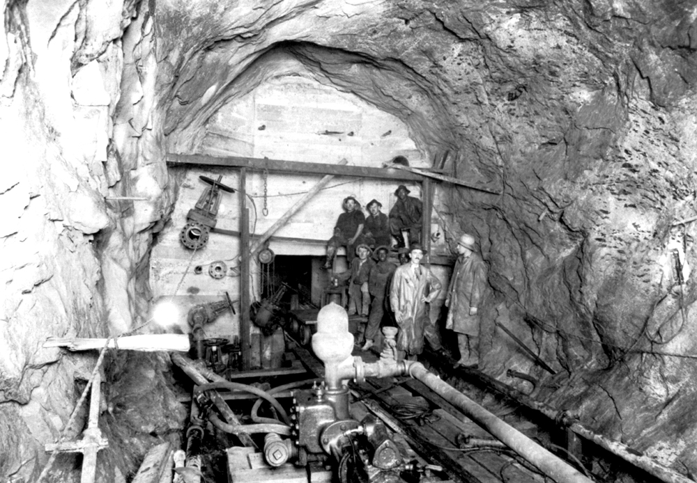 A black and white photo of an underground tunnel under construction. It looks to be about two stories tall and wide. there are a group of men, dirty from working underground, gathered looking at the camera. There are rail tracks inside the tunnel and various equipment erected inside the tunnel.