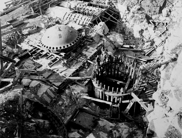 A birds eye view looking down at a construction zone of excavated earth. There is a large steel dome and another one beside it under construction, revealing the shaft going underground, surrounded by steel beams protruding up into the air. Three men are standing on the rim of this shaft looking up at the camera.