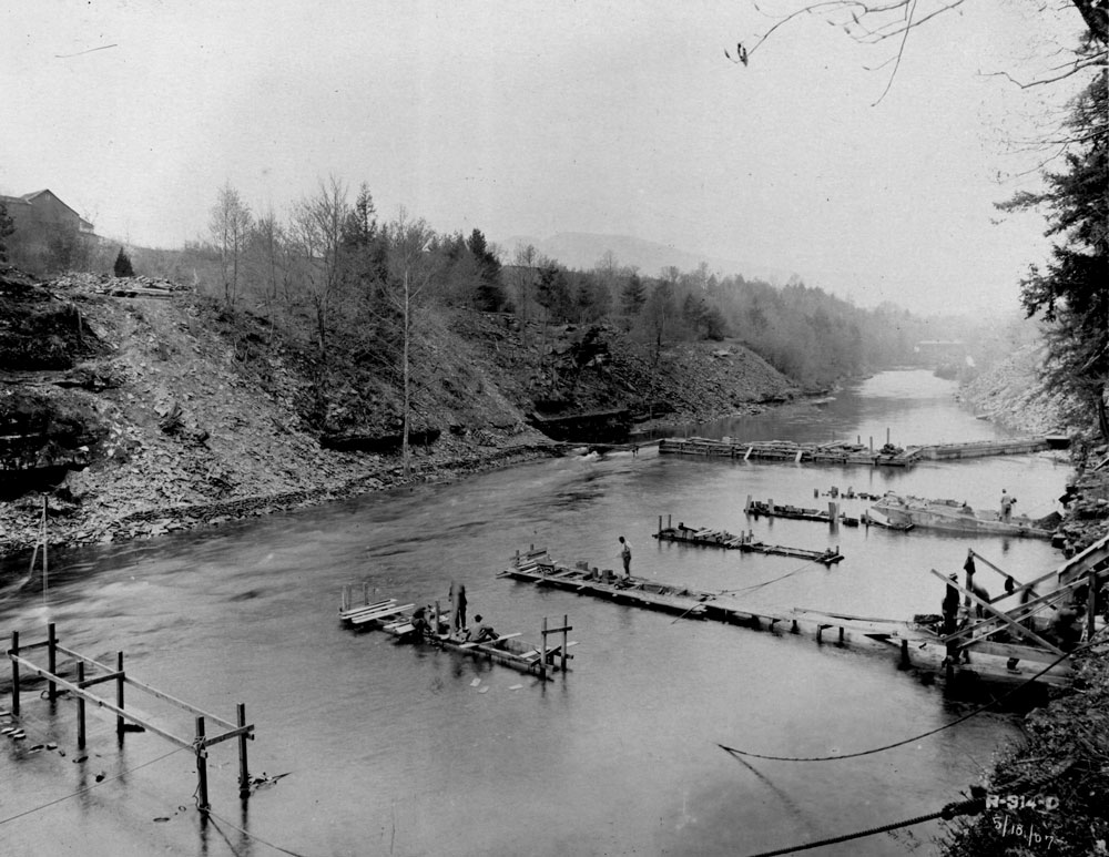 A black and white photo of a body of water with in a narrow valley. There are 5 piers being built across the water and one small dam.