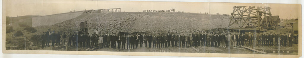 A panoramic black and white photo that has yellowed with age. There is about 70 men lined up in the foreground posing for the photo. Behind them is a dam wall under construction and on top of the dam wall there is another group of figures standing in a line.