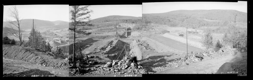 A panoramic photo made of three black and white photos pieced together. The camera is looking down into the valley under construction. The valley construction spreads way into the background on the left, surrounded by mountain ranges off in the distance.