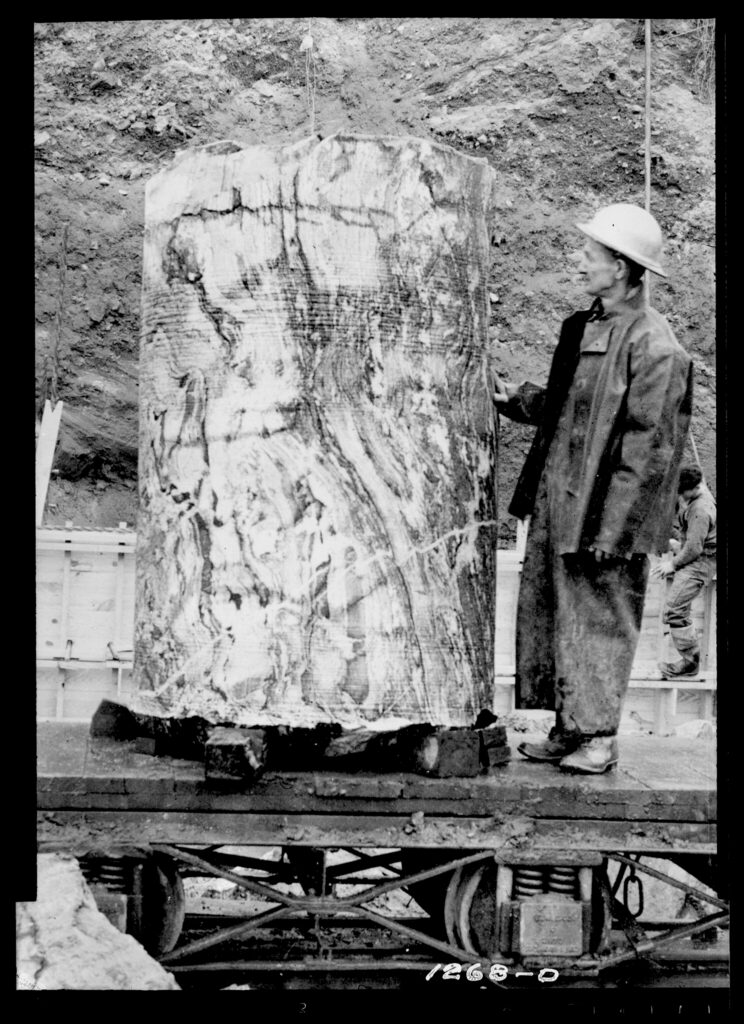 A black and white photo of a man standing next to a column of rock that is taller than he is. It is about 4 ft wide.