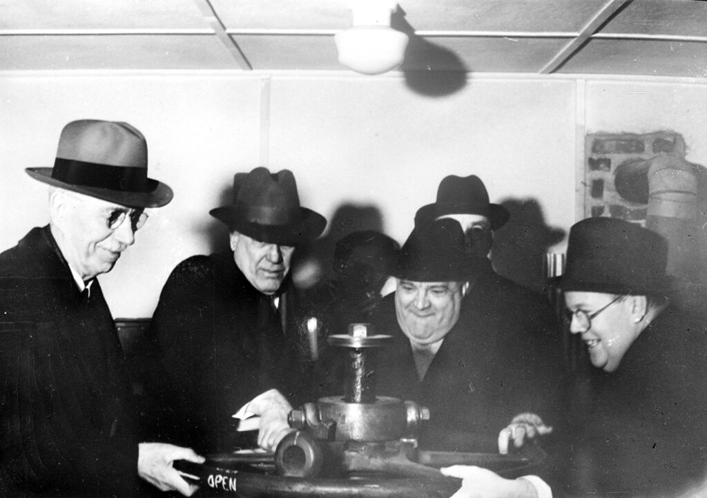 A black and white photo of four men in hats in a low-ceilinged room gathered around a horizontal wheel that they all have their hands on and are turning.